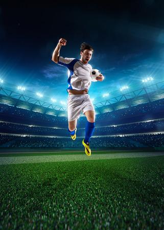 夜のスタジアムの背景にアクションのサッカー選手