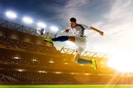 uniforme de futbol: Jugador de f�tbol en acci�n sobre fondo estadio noche