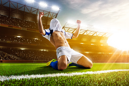 Soccer player in action on night stadium background