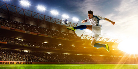soccer ball on grass: Soccer player in action on night stadium background panorama