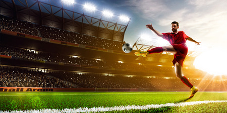 Soccer player in action on night stadium background panorama