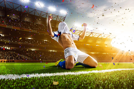 soccer ball on grass: Soccer player in action on night stadium panorama background Stock Photo