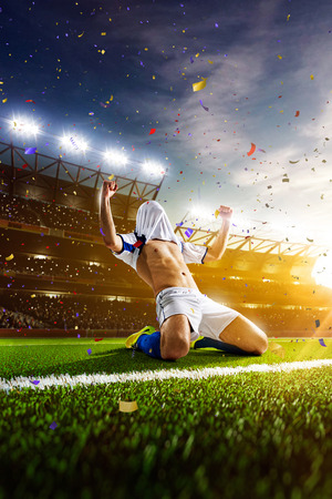 soccer uniforms: Soccer player in action on night stadium panorama background Stock Photo