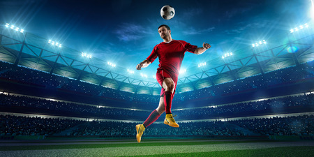 soccer uniforms: Soccer player in action on night stadium background