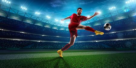 jugador de futbol: Jugador de f�tbol en acci�n sobre fondo estadio noche
