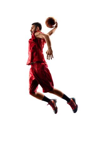 Geïsoleerd op wit basketbalspeler in actie vliegt hoog