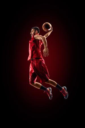 Geïsoleerd op zwart basketbalspeler in actie vliegt hoog Stockfoto