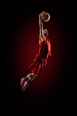 黒に分離されたアクションのバスケット ボール選手は高く飛んで 写真素材