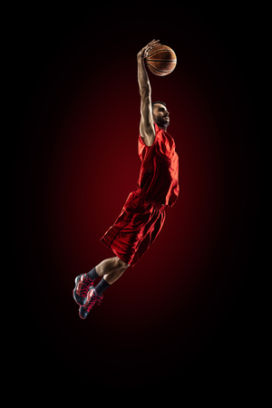 basket ball: Isolated on black basketball player in action is flying high