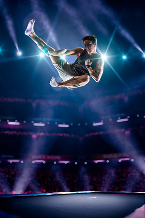 trampoline: Young man is jumping on the trampoline Stock Photo