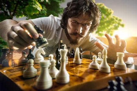 jugando ajedrez: Hombre muy serio está jugando el ajedrez
