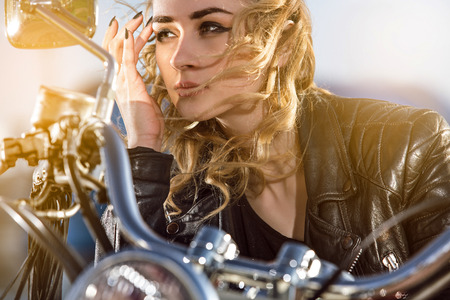 rebel: Biker girl in the  leather jacket on a motorcycle looking at the sunset.