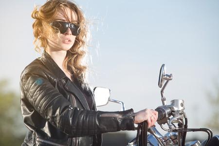 mujer sola: Muchacha del motorista en la chaqueta de cuero en una motocicleta mirando la puesta de sol. Foto de archivo