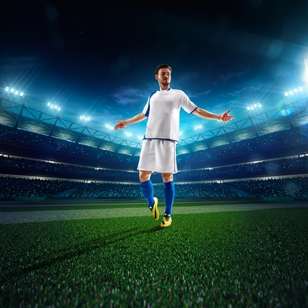 kick ball: Soccer player in action on night stadium panorama background Stock Photo