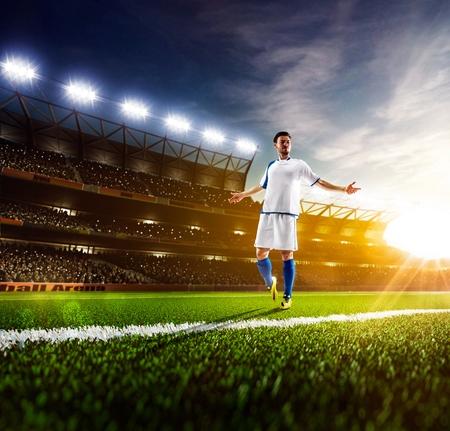 日当たりの良いスタジアム パノラマ背景にアクションのサッカー選手