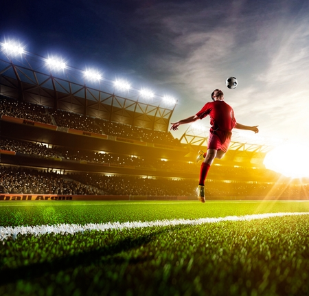 soccer uniforms: Soccer player in action on sunny stadium background