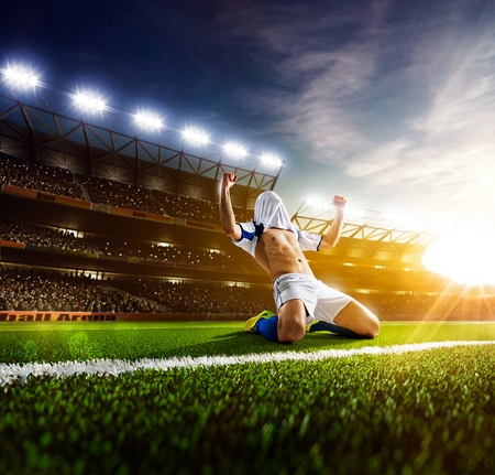 Jugador de fútbol en acción sobre fondo estadio Foto de archivo