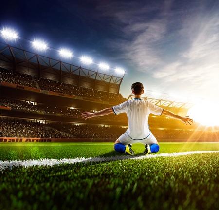 夜のスタジアムのパノラマ背景にアクションのサッカー選手