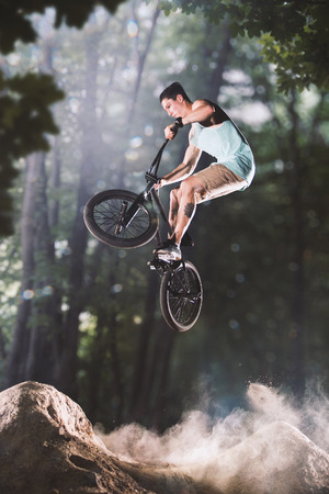 bmx bike: bmx bicycle rider tricking on the forest hills