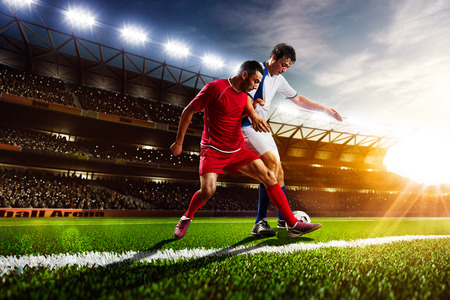 adult foot: Soccer players in action on sunset stadium background panorama