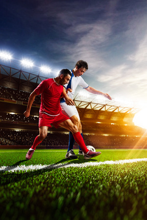 an action: Soccer players in action on sunset stadium background panorama