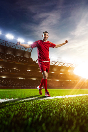 Soccer player in action on sunset stadium background panorama Stock Photo