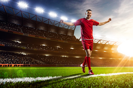 jugador de futbol: Jugador de fútbol en acción en estadio atardecer de fondo panorama