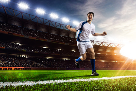 athletes: Soccer player in action on sunset stadium background panorama Banque d'images