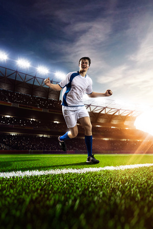 to soccer: Jugador de f�tbol en acci�n sobre fondo estadio atardecer