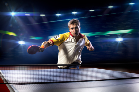 sports backgrounds: young sports man tennis player is playing on black background with lights