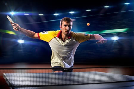 table tennis: young sports man tennis player is playing on black background with lights
