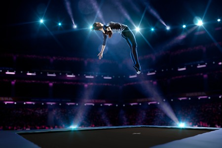 gymnastics: Young girl is jumping on the trampoline Stock Photo