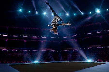 Jong meisje is springen op de trampoline