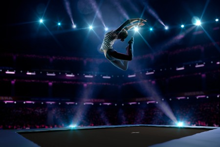 gymnastics sports: Young girl is jumping on the trampoline Stock Photo