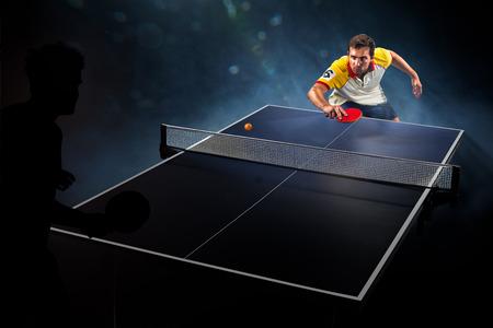 jugando tenis: deporte joven jugador de tenis hombre está jugando en el fondo negro con luces Foto de archivo