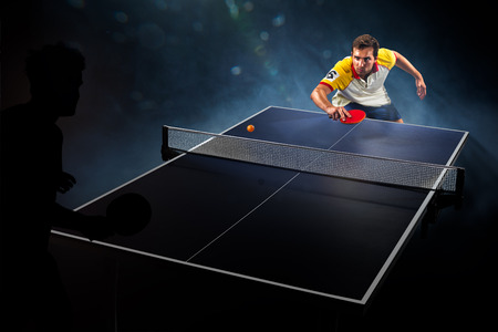 table: young sports man tennis player is playing on black background with lights