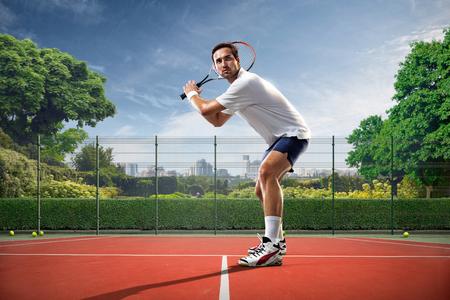 jugando tenis: Hombre joven que juega a tenis en día soleado