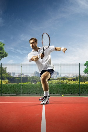 젊은 남자가 맑은 날에 테니스를 치고있다. 스톡 콘텐츠