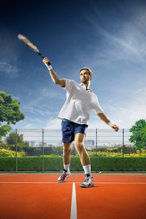 Young man is playing tennis on sunny day