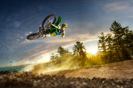 red soil: Dirt bike rider is flying high in evening Stock Photo