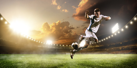 Soccer player in action on sunset stadium background Foto de archivo
