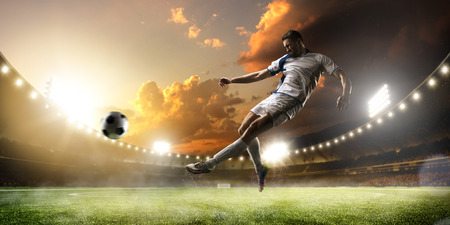 kick ball: Soccer player in action on sunset stadium background Stock Photo