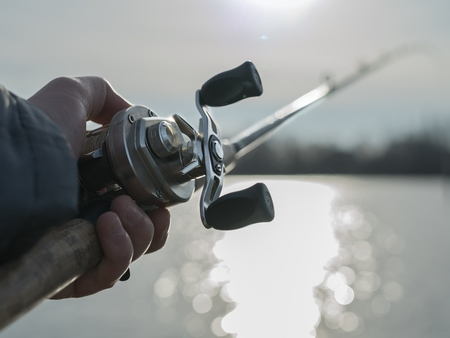 hand crank: Angler on the river with close up baitcasting reel in hilights