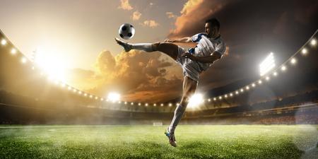 patada: Jugador de fútbol en acción sobre fondo estadio atardecer