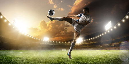 Soccer player in action on sunset stadium background