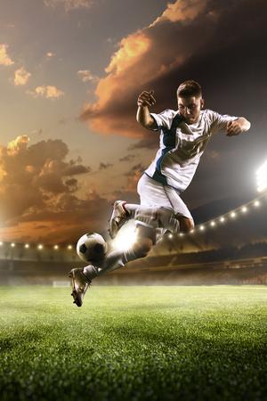 背景の夕焼けスタジアムにアクションのサッカー選手