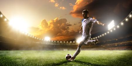 Soccer player in action on sunset stadium background Foto de archivo