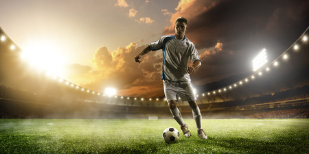 soccer uniforms: Soccer player in action on sunset stadium background Stock Photo