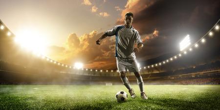 stadium: Soccer player in action on sunset stadium background Stock Photo