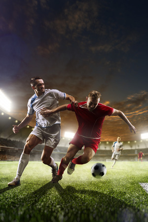 Soccer players in action on sunset stadium background panorama